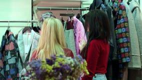 Due ragazze camminano in un negozio di vestiti, esaminano i vestiti e lo provano sopra archivi video