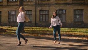 Due ragazze caucasiche impressionanti stanno ballando insieme sulla via in Sunny Light Day, essendo ispirate e felici, mostrando stock footage
