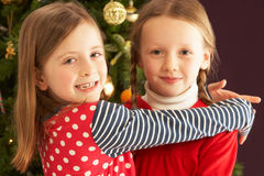Due ragazze che abbracciano davanti all'albero di Natale Immagini Stock
