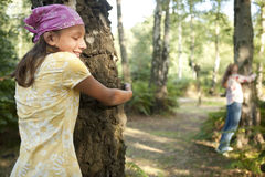 Due ragazze che abbracciano gli alberi in foresta Fotografie Stock Libere da Diritti