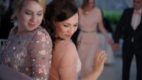 Due ragazze che ballano al partito Amici in vestiti da sera all'evento: nozze, compleanno o festa stock footage