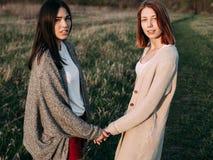 Due ragazze che camminano su un campo di erba Immagini Stock