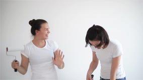 Due ragazze che cantano nel rullo di pittura, amici stanno facendo le riparazioni e ballare stock footage
