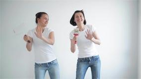 Due ragazze che cantano nel rullo di pittura, amici stanno facendo le riparazioni e ballare archivi video