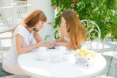 Due ragazze che esaminano telefono cellulare Fotografia Stock