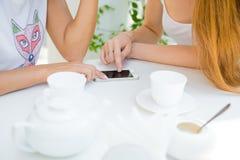 Due ragazze che esaminano telefono cellulare Immagine Stock