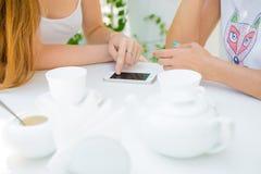 Due ragazze che esaminano telefono cellulare Immagini Stock Libere da Diritti