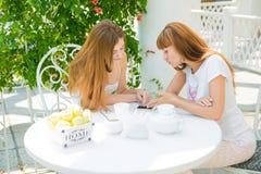 Due ragazze che esaminano telefono cellulare Fotografie Stock