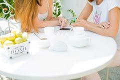 Due ragazze che esaminano telefono cellulare Fotografie Stock Libere da Diritti