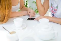 Due ragazze che esaminano telefono cellulare Immagine Stock Libera da Diritti