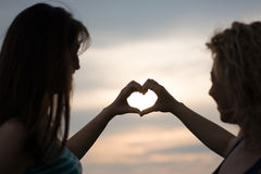Due ragazze che fanno forma del cuore Fotografia Stock