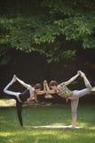 Due ragazze che fanno gli esercizi di yoga in parco Fotografie Stock Libere da Diritti