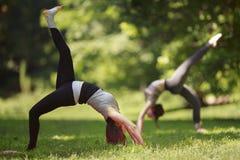 Due ragazze che fanno gli esercizi di yoga in parco Immagini Stock Libere da Diritti