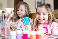 Due ragazze che fanno le decorazioni di Pasqua a casa immagini stock libere da diritti