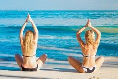 Due ragazze che fanno le pose di yoga sul mar dei Caraibi Immagini Stock