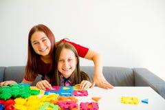 Due ragazze che giocano con i blocchetti della costruzione immagini stock