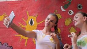 Due ragazze che giocano con il filatore e fanno la foto sul cellulare, gioco degli amici con il giocattolo per distensione della  stock footage