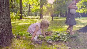 Due ragazze che giocano nel parco sull'erba vicino all'albero video d archivio