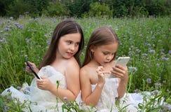 Due ragazze che giocano nel telefono e nella compressa Fotografia Stock