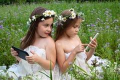 Due ragazze che giocano nel telefono e nella compressa Immagine Stock