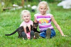 Due ragazze che giocano sull'erba verde Fotografia Stock Libera da Diritti