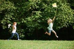 Due ragazze che inseguono le farfalle nel campo di estate immagine stock libera da diritti