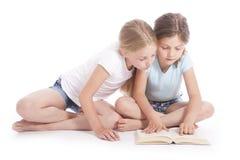 Due ragazze che leggono insieme un libro Immagini Stock Libere da Diritti