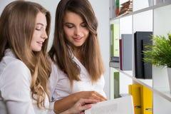 Due ragazze che leggono un libro in ufficio Immagini Stock Libere da Diritti