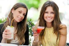 Due ragazze che mangiano un aperitivo all'aperto fotografia stock
