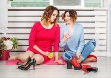 Due ragazze che parlano e che bevono tè nella stanza Immagini Stock