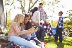 Due ragazze che per mezzo del telefono cellulare su vacanza in campeggio della famiglia Fotografie Stock