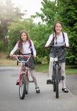 Due ragazze che permutano alla scuola sulle biciclette Fotografie Stock
