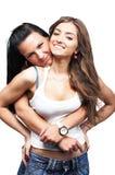 Due ragazze che portano le blue jeans su bianco Fotografia Stock