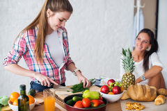 Due ragazze che preparano cena in un concetto della cucina fotografia stock libera da diritti