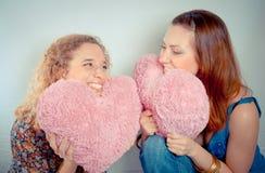 Due ragazze che ridono e che tengono i cuori immagine stock