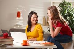 Due ragazze che ridono insieme alla tabella Fotografia Stock