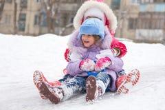 Due ragazze che rotolano gli scorrevoli del ghiaccio Fotografie Stock