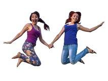 Due ragazze che saltano nel tenersi per mano dell'aria fotografia stock libera da diritti