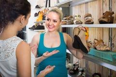 Due ragazze che scelgono le scarpe nel deposito Fotografia Stock