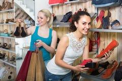 Due ragazze che scelgono le scarpe nel deposito Immagini Stock