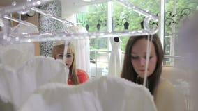 Due ragazze che scelgono un vestito da sposa video d archivio
