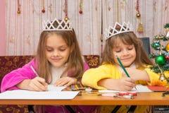 Due ragazze che scrivono felicemente lettera a Santa Claus che si siede ad uno scrittorio nell'ambiente familiare Immagini Stock