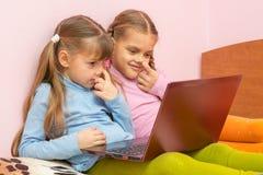 Due ragazze che selezionano il suo naso e che esaminano lo schermo del computer portatile Fotografia Stock Libera da Diritti