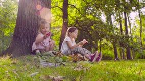 Due ragazze che si siedono nel parco e che mangiano granato stock footage