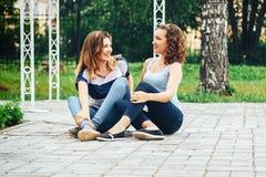 Due ragazze che si siedono nella conversazione e nello smilind del parco, ridenti, Fotografia Stock Libera da Diritti