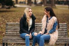 Due ragazze che si siedono sul banco all'aperto Immagine Stock