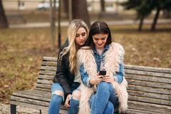 Due ragazze che si siedono sul banco all'aperto Immagine Stock Libera da Diritti