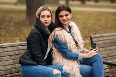 Due ragazze che si siedono sul banco all'aperto Fotografia Stock Libera da Diritti