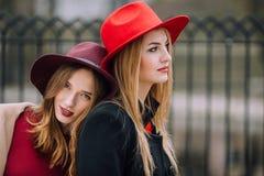 Due ragazze che si siedono sul banco e sul sorriso Fotografie Stock Libere da Diritti