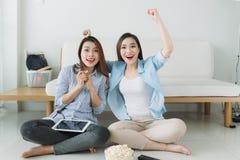 Due ragazze che si siedono sul pavimento vicino allo strato guardano un movimento Immagine Stock